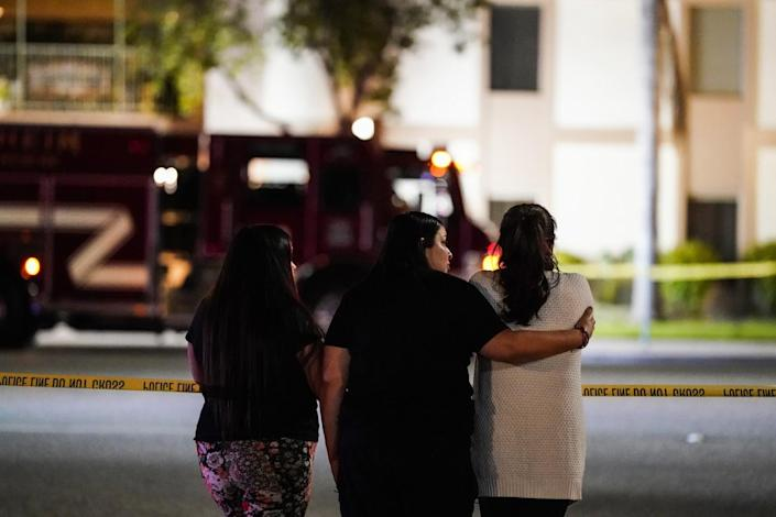 Three women, one with her arm around another, gather across from the scene of a multiple shooting