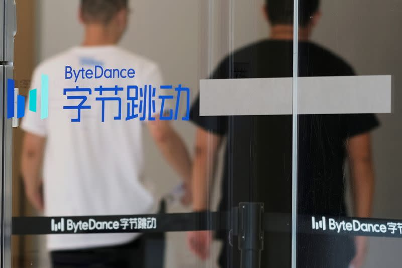 FILE PHOTO: People walk past a logo of Bytedance, which owns short video app TikTok, at its office in Beijing