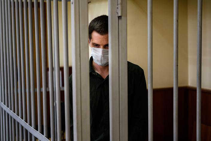 Former U.S. Marine Trevor Reed, charged with attacking police, stands inside a defendants' cage during his verdict hearing at Moscow's Golovinsky district court on July 30, 2020. / Credit: DIMITAR DILKOFF