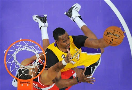 Los Angeles Lakers center Dwight Howard, right, puts up a shot as Washington Wizards center Jason Collins defends during the first half of an NBA basketball game, Friday, March 22, 2013, in Los Angeles. (AP Photo/Mark J. Terrill)