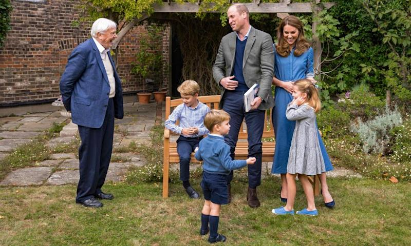 The Duke and Duchess of Cambridge and Prince George (seated), Princess Charlotte and Prince Louis with Sir David Attenborough (L) in the gardens of Kensington Palace.