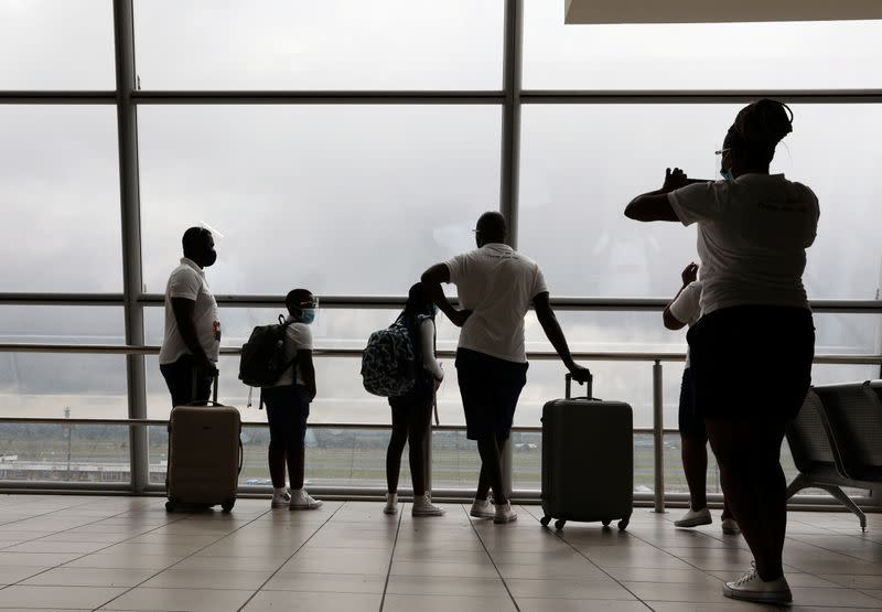 A woman photographs her family members before boarding a plane at the O.R. Tambo International Airport in Johannesburg