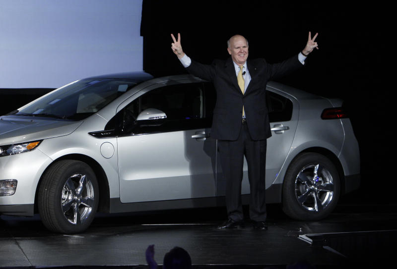 General Motors chief executive officer Dan Akerson raises his arms next to the Chevrolet Volt with the first vehicle identification number at the General Motors Hamtramck assembly plant in Hamtramck, Mich., Tuesday, Nov. 30, 2010. (AP Photo/Paul Sancya)