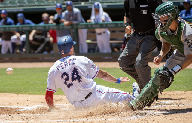 Texas Rangers' Hunter Pence (24) scores on a single by Asdrubal Cabrera off of Oakland Athletics starting pitcher Paul Blackburn as catcher Nick Hundley receives the late throw during the first inning of the first baseball game of a doubleheader Saturday, June 8, 2019, in Arlington, Texas. Elvis Andrus also scored on the play. (AP Photo/Jeffrey McWhorter)