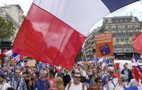"""Protestors hold signs which read in French, """"freedom"""" and 'no to the vaccine passport"""" as they attend a demonstration in Paris, France, Saturday, July 31, 2021. Demonstrators gathered in several cities in France on Saturday to protest against the COVID-19 pass, which grants vaccinated individuals greater ease of access to venues. (AP Photo/Michel Euler)"""