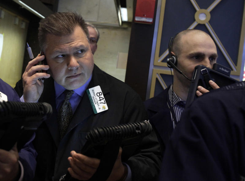 Trader George Ettinger, left, works on the floor of the New York Stock Exchange, Friday, May 11, 2012. Major bank stocks fell sharply Friday after JPMorgan Chase surprised investors by announcing a $2 billion trading loss. (AP Photo/Richard Drew)