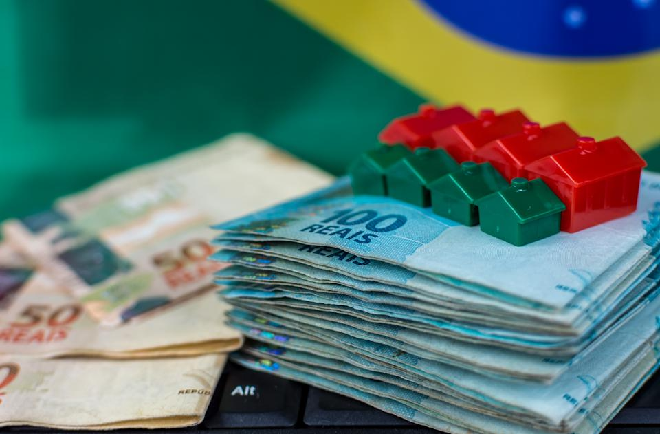 houses with coins and miniature brazilian money banknotes focusing on financial operations