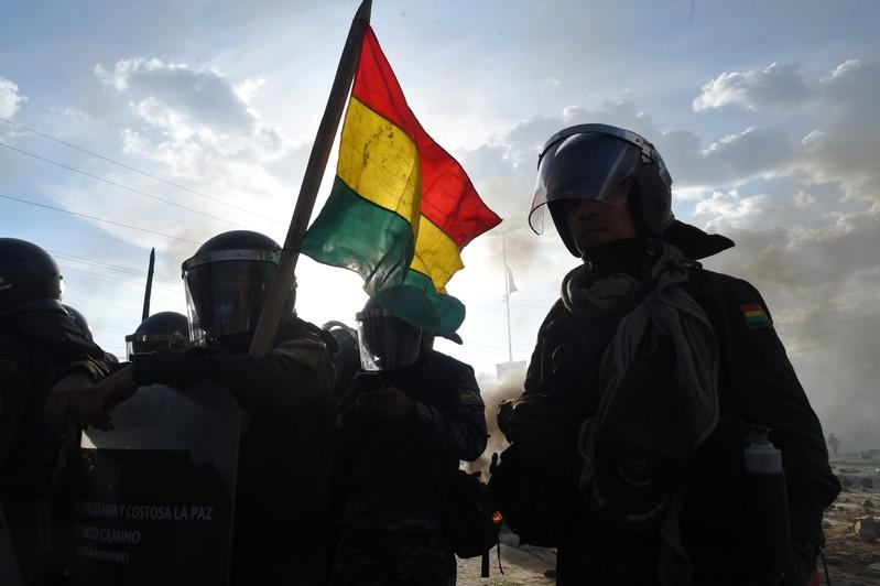 Silhouettes of riot police officers are seen in Sacaba