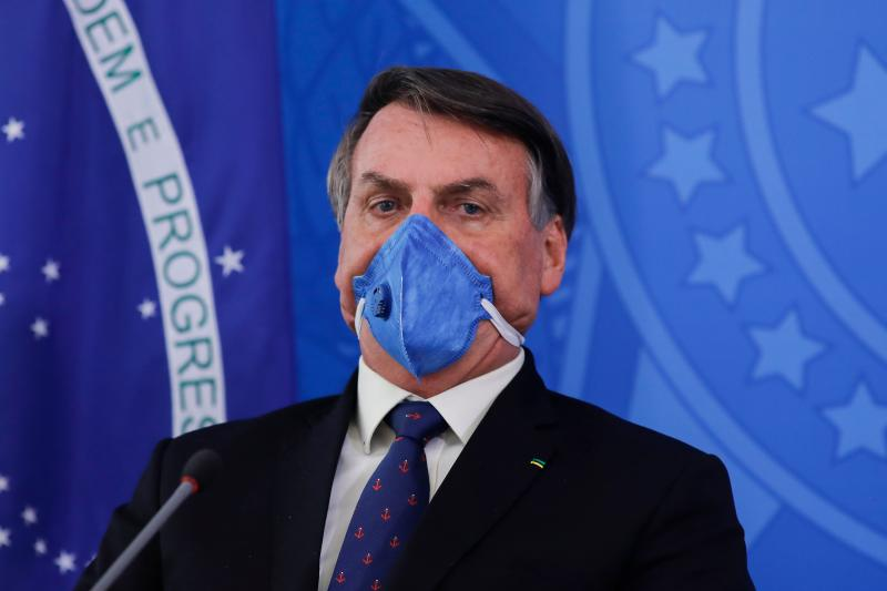 Brazil's President Jair Bolsonaro wears a face mask during a press conference on the coronavirus pandemic COVID-19 at the Planalto Palace in Brasilia, Brazil on March 20, 2020. - Brazil's government on Friday drastically downgraded its growth projections for 2020 by 2.1 percent to practically zero (0.02 percent) due to the coronavirus pandemic. (Photo by Sergio LIMA / AFP) (Photo by SERGIO LIMA/AFP via Getty Images)