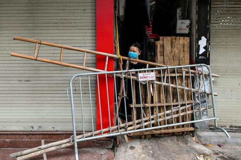 A woman looks out from behind an improvised barricade made of wooden planks and a ladder to restrict people's movements in Hanoi (AFP/Manan VATSYAYANA)