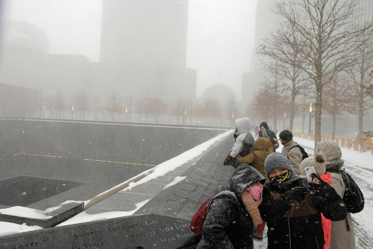Tourists stop to photograph themselves at the National September 11 Memorial & Museum during a snowstorm in New York, U.S., January 4, 2018.  REUTERS/Lucas Jackson
