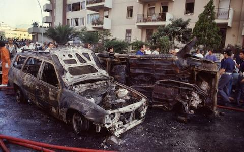 Burnt-out cars after the bomb attack which killed anti-mafia investigator Paolo Borsellino in 1992 - Credit: Tony Gentile/Reuters