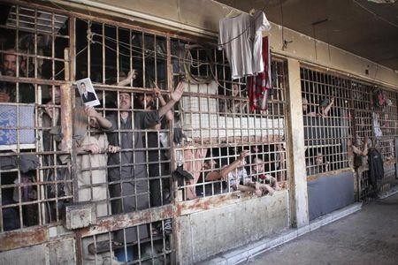 Inmates are seen behind bars in Aleppo's main prison