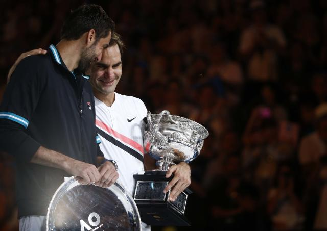 Tennis - Australian Open - Men's singles final - Rod Laver Arena, Melbourne, Australia, January 28, 2018. Winner Roger Federer of Switzerland cries while holding the trophy as runner-up Marin Cilic of Croatia looks on. REUTERS/Thomas Peter