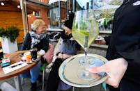 A waitress serves drinksin the outdoor part of a cafe in Tuebingen
