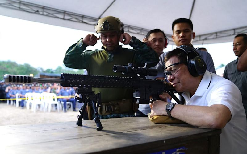 Rodrigo Duterte firing a few rounds with a sniper rifle during the opening ceremony of the National Special Weapons and Tactics. His relationship with the UN is becoming increasingly strained - AFP