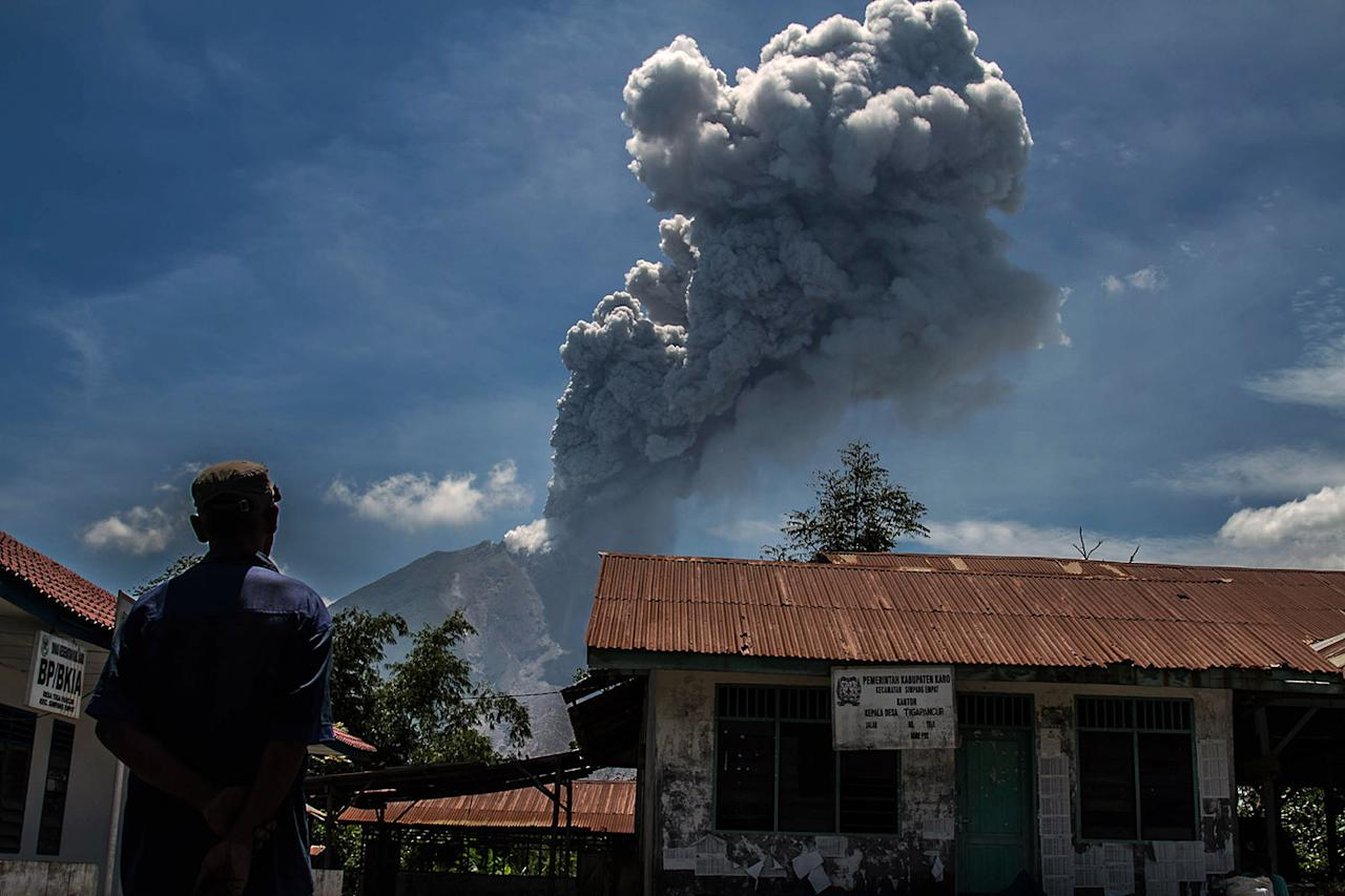 <p>A resident watched as Sinabung volcano spews rolling thick volcanic ash into the air, as seen from Tiga Pancur village, North Sumatra province, Indonesia, May 25, 2017. (Photo: Ivan Damanik via ZUMA Wire) </p>