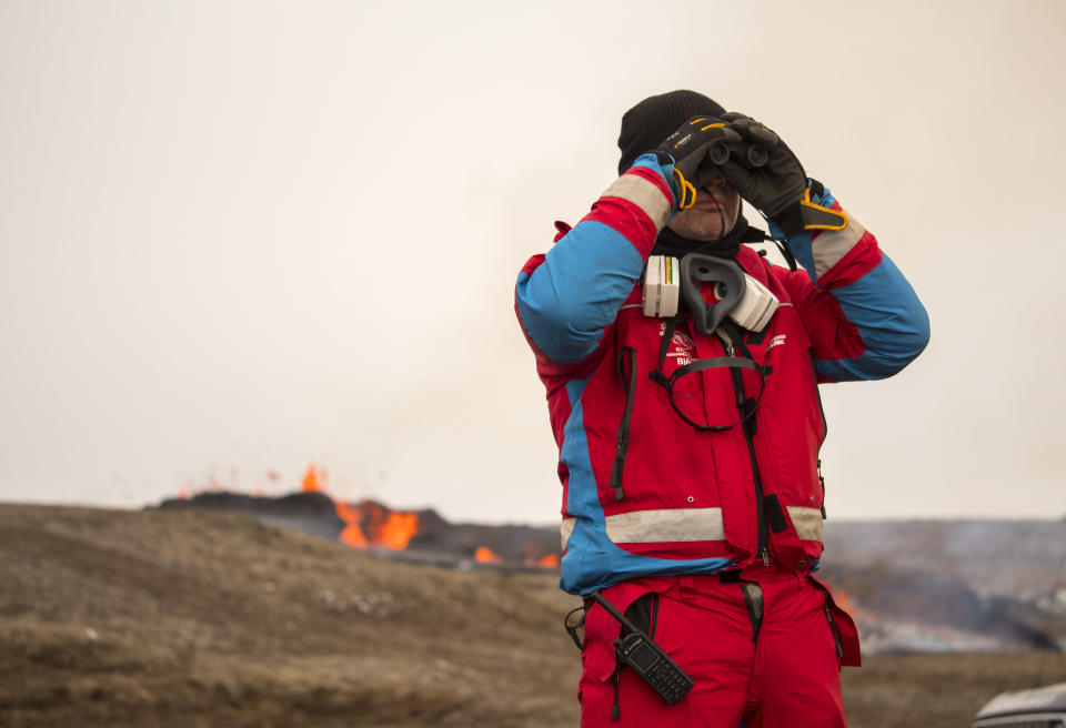 A member of the Search and Rescue Team, Bjorgunasveit scans the horizon near a new fissure on a volcano on the Reykjanes Peninsula in southwestern Iceland, Monday, April 5, 2021. The new fissure has opened up at the Icelandic volcano that began erupting last month, prompting the evacuation of hundreds of hikers who had come to see the spectacle. Officials say the new fissure is about 500 meters (550 yards) long and about one kilometer (around a half-mile) from the original eruption site in the Geldinga Valley (AP Photo/Marco Di Marco)