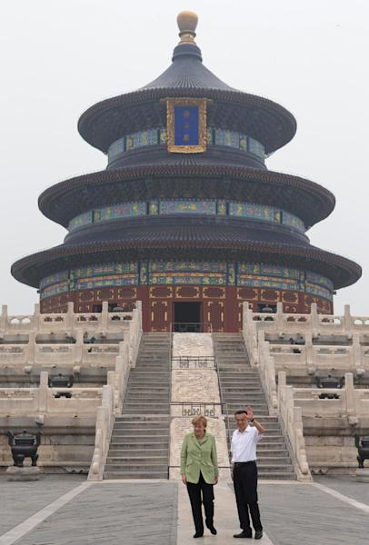 Angela Merkel and Li Keqiang wave during a visit to the Temple of Heaven in Beijing on July 7, 2014 (AFP Photo/Rolex Dela Pena)