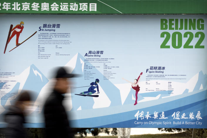 """FILE - In this Feb. 6, 2019, file photo, people walk past a display introducing winter sporting events for the upcoming 2022 Beijing Winter Olympics at a temple fair at Longtan Park in Beijing. Groups alleging human-rights abuses in China are calling for a full boycott of the Beijing Olympics, which is sure to ratchet up pressure on the International Olympic Committee, athletes, sponsors, and sports federations. A coalition of activists representing Uyghurs, Tibetans, residents of Hong Kong and others, issued a statement Monday, May 17, 2021 calling for the """"full boycott,"""" eschewing lesser measures like """"diplomatic boycotts"""" and negotiations with the IOC or China. (AP Photo/Mark Schiefelbein, File)"""