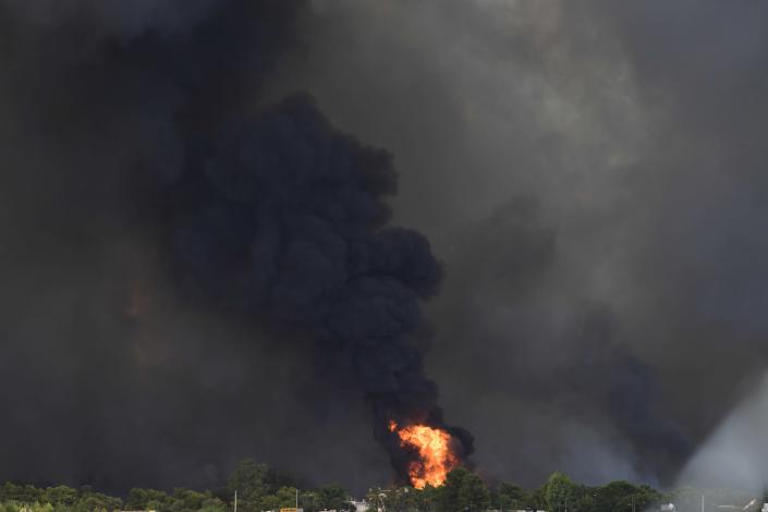 Flames burn near buildings outside an Air Base in Tatoi area, northern Athens, Greece, Tuesday, Aug. 3, 2021. Greece Tuesday grappled with the worst heatwave in decades that strained the national power supply and fueled wildfires near Athens and elsewhere in southern Greece. As the heat wave scorching the eastern Mediterranean intensified, temperatures reached 42 degrees Celsius (107.6 Fahrenheit) in parts of the Greek capital. (AP Photo/Michael Varaklas)
