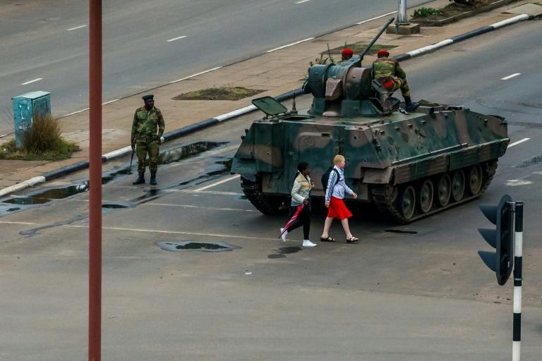 Young women walk past an armoured personnel carrier in Harare