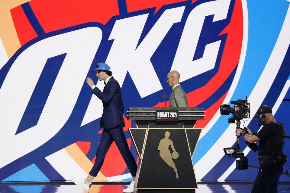 CORRECTS SPELLING TO GIDDEY, INSTEAD OF GIDDY - CORRECTS TEAM TO OKLAHOMA CITY THUNDER, INSTEAD OF GOLDEN STATE WARRIORS - Josh Giddey, left, walks off the stage with NBA Commissioner Adam Silver after being selected sixth overall by the Oklahoma City Thunder during the NBA basketball draft, Thursday, July 29, 2021, in New York. (AP Photo/Corey Sipkin)