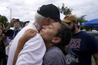 Rachel Spiegel, right, is hugged by the Mayor of Surfside Charles Burkett, left, as she asks for information about the 12-story beachfront condo building which partially collapsed, Saturday, June 26, 2021, in the Surfside area of Miami. Spiegel's mother Judy lives in the building and is missing. (AP Photo/Lynne Sladky)