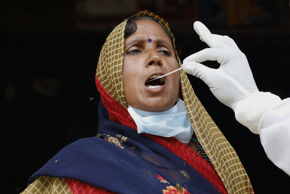 A health worker takes a swab sample of a woman to test for COVID-19 in Kusehta village north of Prayagraj, India, Saturday, May 29, 2021. (AP Photo/Rajesh Kumar Singh)