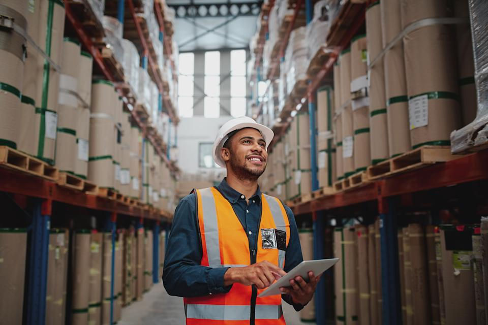 Portrait of young man wearing safety jacket holding digital tablet standing in factory warehouse