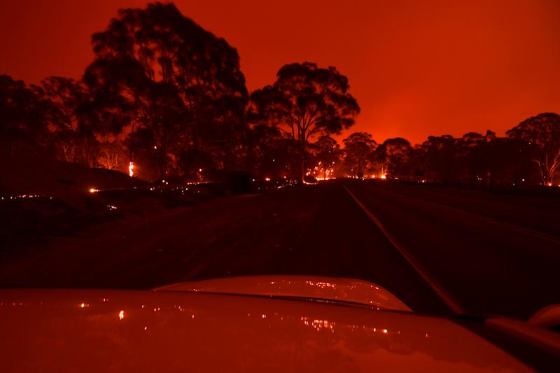 The afternoon sky glows orange from bushfires in the area around the town of Nowra in the Australian state of New South Wales on December 31, 2019. - Thousands of holidaymakers and locals were forced to flee to beaches in fire-ravaged southeast Australia on December 31, as blazes ripped through popular tourist areas leaving no escape by land. (Photo by Saeed KHAN / AFP) (Photo by SAEED KHAN/AFP via Getty Images)