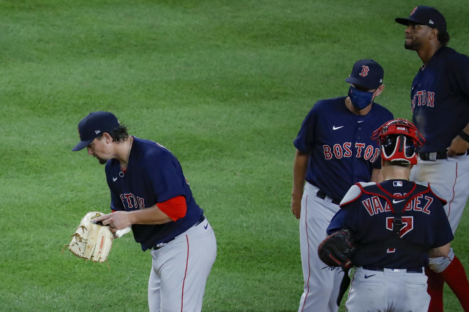 Boston Red Sox starting pitcher Zack Godley, left, is relieved by manager Ron Roenicke, center right, in the fourth inning of a baseball game against the New York Yankees, Saturday, Aug. 1, 2020, in New York. (AP Photo/John Minchillo)
