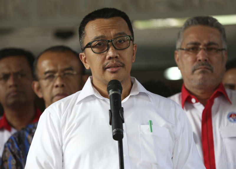 Indonesian Youth and Sports Minister Imam Nahrawi, center, speaks to the media during a press conference in Jakarta, Indonesia, Thursday, Sept. 19, 2019. Nahrawi has stepped down from his position after being named a bribery suspect by the country's anti-graft commission. (AP Photo/Tatan Syuflana)