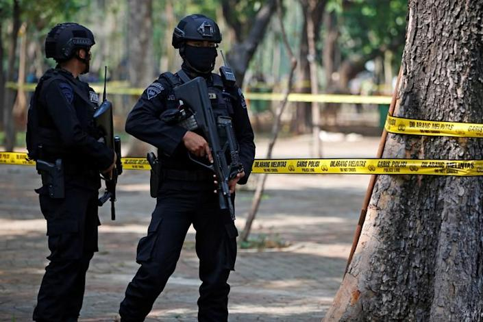 Armed police officers stand guard following a blast at National Monument (Monas) complex in Jakarta