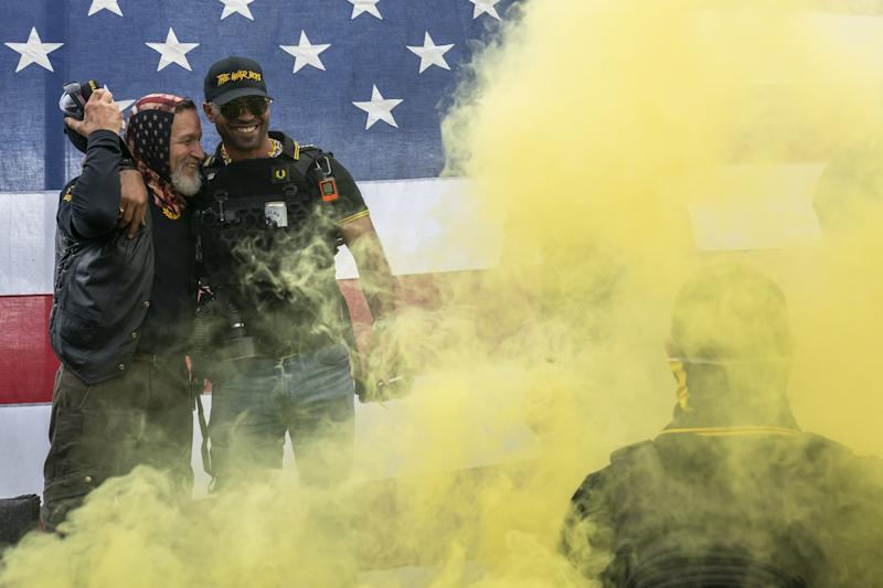 Yellow smoke rises around men in Proud Boys gear in front of a U.S. flag