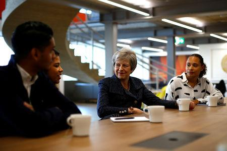 Britain's Prime Minister Theresa May talks to employees at WPP who have come through micro fellowships and apprenticeships, after a roundtable meeting with business leaders whose companies are inaugural signatories of the Race at Work Charter, at the Southbank Centre in London, Britain, October 11, 2018. REUTERS/Henry Nicholls