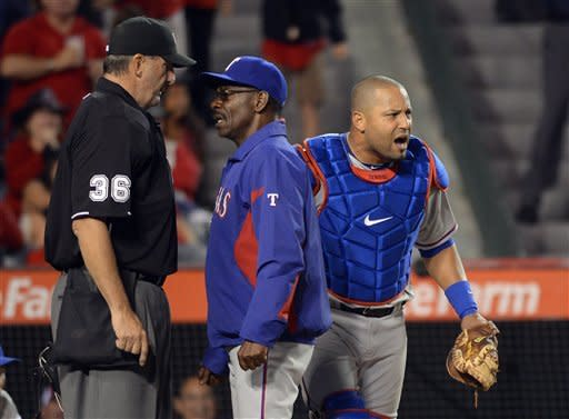 Texas Rangers manager Ron Washington, center, argues with home plate umpire Tim McClelland, left, as catcher Yorvit Torrealba reacts after Los Angeles Angels' Mike Trout was called safe at home on a sacrifice fly by Kendrys Morales during the seventh inning of their baseball game, Saturday, June 2, 2012, in Anaheim, Calif. Torrealba was thrown out of the game while arguing with the umpire on the play. (AP Photo/Mark J. Terrill)