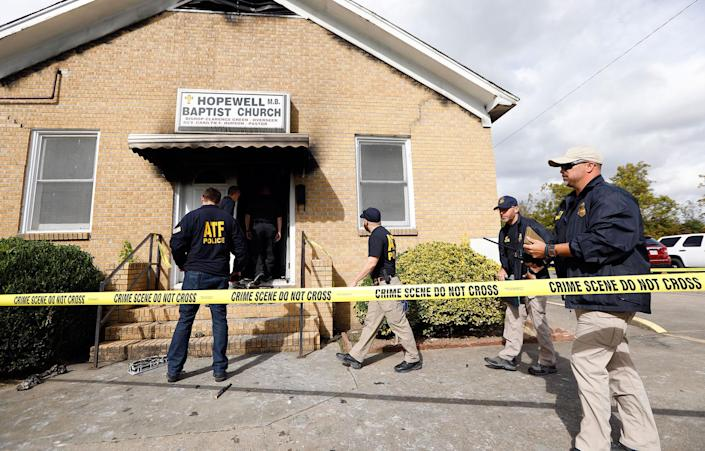 """<p>ATF agents gather outside the fire damaged Hopewell M.B. Baptist Church in Greenville, Miss., Wednesday, Nov. 2, 2016. """"Vote Trump"""" was spray-painted on an outside wall of the black member church. (AP Photo/Rogelio V. Solis) </p>"""