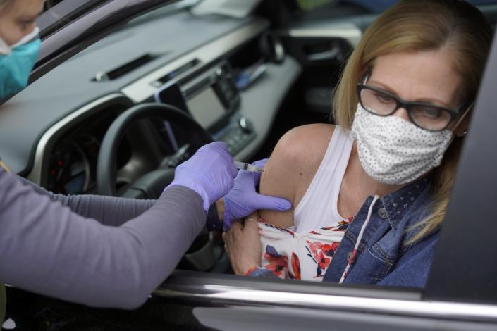 Kerry Burke gets her second COVID-19 vaccination at a mobile clinic in Great Barrington, Mass., Monday, April 12, 2021. This particular clinic used the Moderna vaccine. (Ben Garver/The Berkshire Eagle via AP)