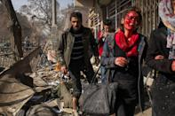 <p>Rahela, her face bloodied by shattered glass from the shop where she had been with her sister (right), is helped from the scene of a street bombing in Kabul, Afghanistan, before being taken to hospital. (Andrew Quilty) </p>