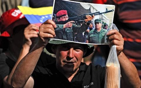 A Venezuelan government supporter holds a picture of late president Hugo Chavez during a rally in Caracas on May 20, 2019 - Credit: AFP