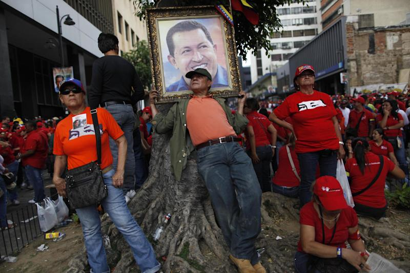A supporter of Venezuela's acting President Nicolas Maduro leans against a tree under a poster of late President Hugo Chavez outside the national electoral council where Maduro registered his presidential candidacy in Caracas, Venezuela, Monday, March 11, 2013.  Presidential elections were announced to take place on April 14, after Maduro announced on March 5 that Chavez had died.  (AP Photo/Rodrigo Abd)
