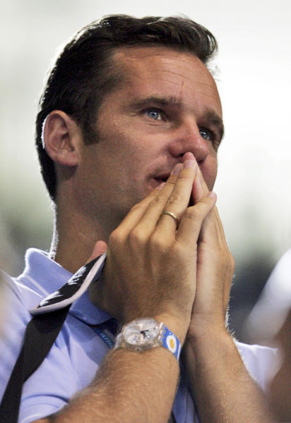 FILE - In this Aug. 20, 2004 file photo Spain's Duke of Palma Inaki Urdangarin and husband of Spain's Princess Cristina reacts while watching a handball match in Athens. Urdangarin, the Spanish king's son-in-law and husband of Princess Cristina will undergo interrogation over alleged corruption Saturday Feb. 25, 2012 in Palma de Mallorca. Although the case file against him remains sealed, much has been leaked and Urdangarin is suspected of using his high-profile position to win contracts from regional governments for a non-profit foundation he ran, then subcontract the work to for-profit companies he also ran, sometimes charging the governments ridiculously inflated prices and stashing at least some of the income in overseas tax havens. The king has dropped Urdangarin like a hot potato, announcing in December his son-in-law would no longer take part in official ceremonies with the rest of the family. (AP Photo/Andrew Medichini, File)