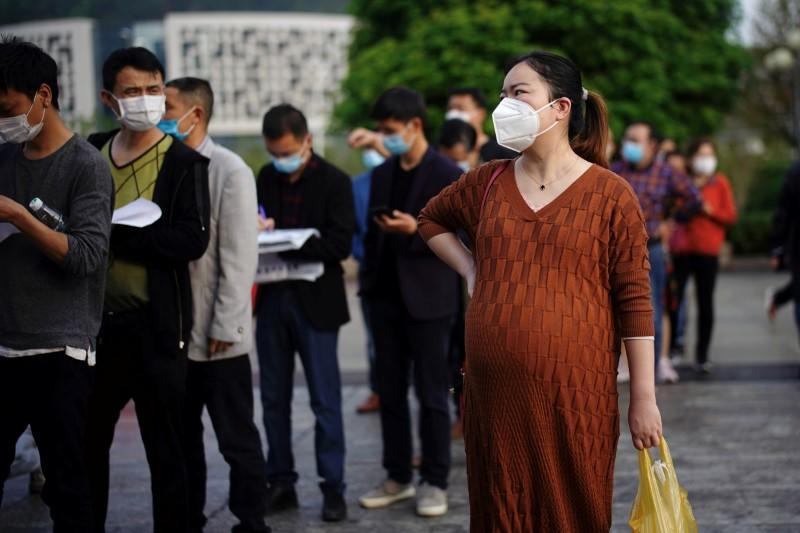 People wearing face masks line up outside Xianning Central Hospital in Xianning