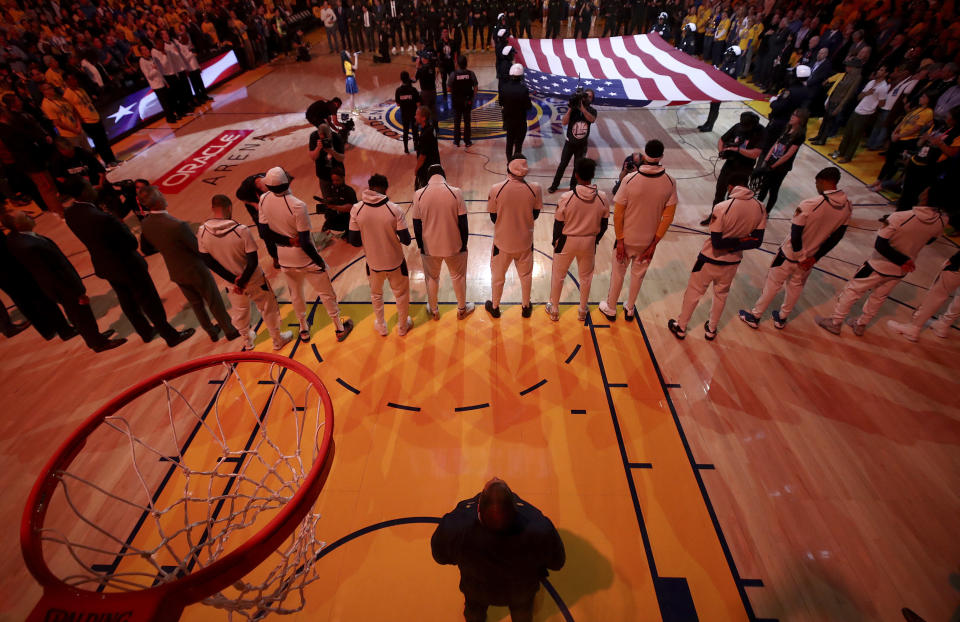 Players listen to the national anthem before Game 1 of the NBA Finals between the Golden State Warriors and Cleveland Cavaliers. (AP)