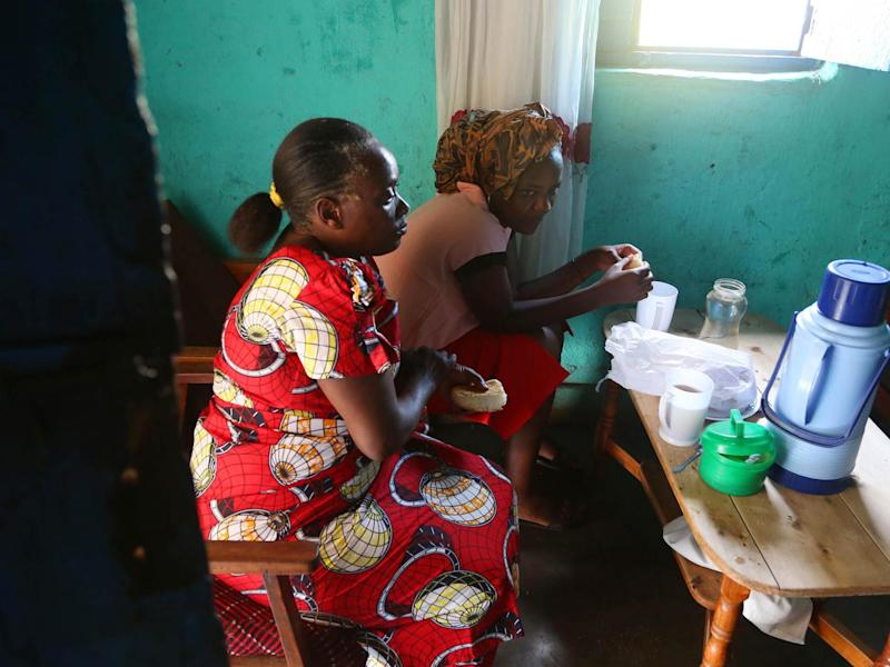 Angel eats bread and drinks tea with her mother Jacqueline, left, at their home before they go to church