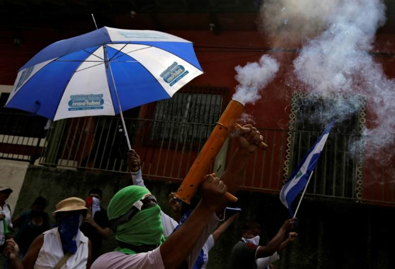 "An anti-government protester fires a homemade mortar during a march dubbed ""United Nicaragua will never be defeated"" in Granada, Nicaragua"