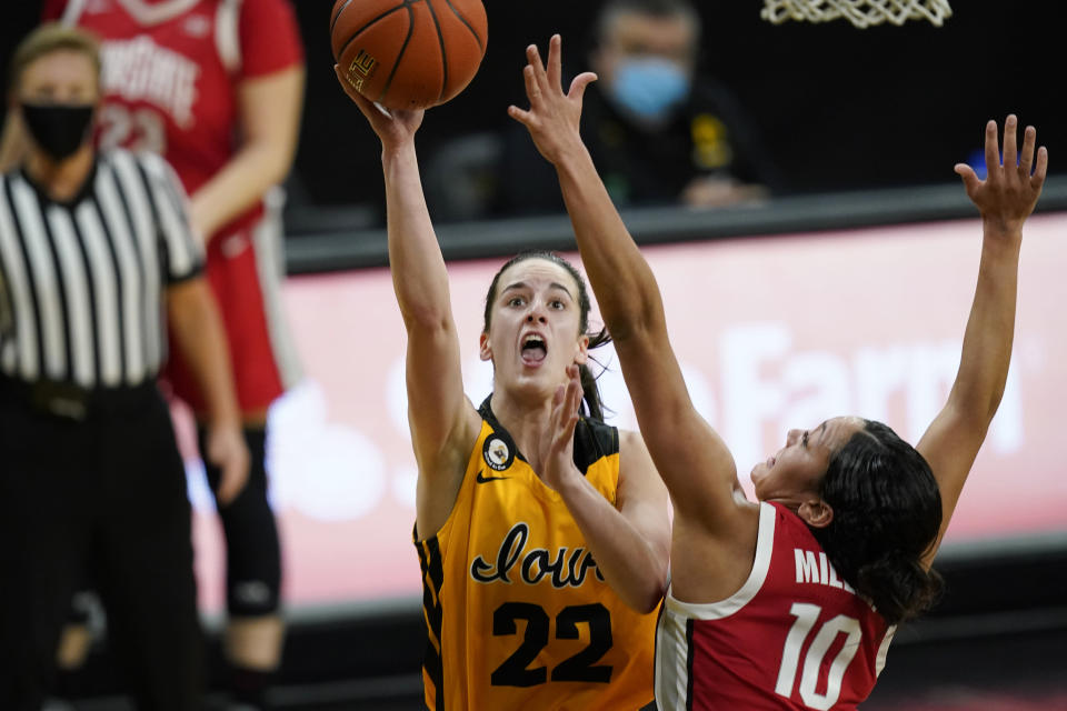 Iowa guard Caitlin Clark (22) drives to the basket ahead of Ohio State guard Braxtin Miller (10) during the first half of an NCAA college basketball game Wednesday, Jan. 13, 2021, in Iowa City, Iowa. Clark, an in-state recruit from West Des Moines Dowling High School, came to the Hawkeyes as a five-star recruit rated No. 4 nationally by ESPN. She won gold medals with the United States team at the 2017 U16 FIBA Americas Tournament and 2019 U19 FIBA World Cup Tournament. It didn't take long for the Hawkeyes to get to know her. (AP Photo/Charlie Neibergall)
