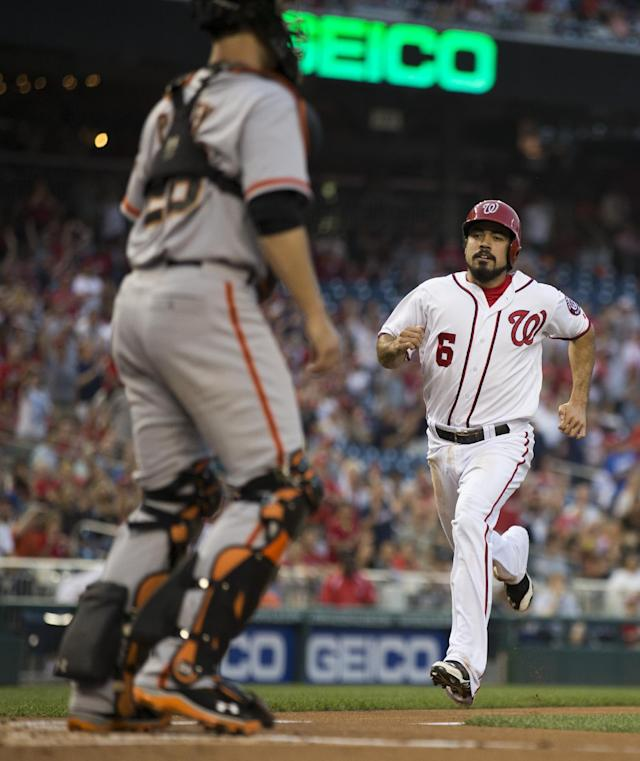 San Francisco Giants catcher Buster Posey, left, stands at home plate as Washington Nationals' Anthony Rendon scores on an error by second baseman Joe Panik during the first inning of a baseball game on Friday, Aug. 22, 2014, in Washington. (AP Photo/Evan Vucci)