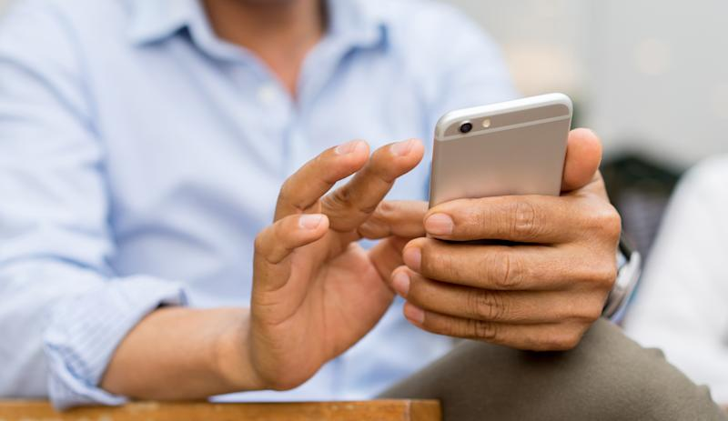 close up mature businessman holding smartphone and checking news from company by texting to employee , business and technology concept